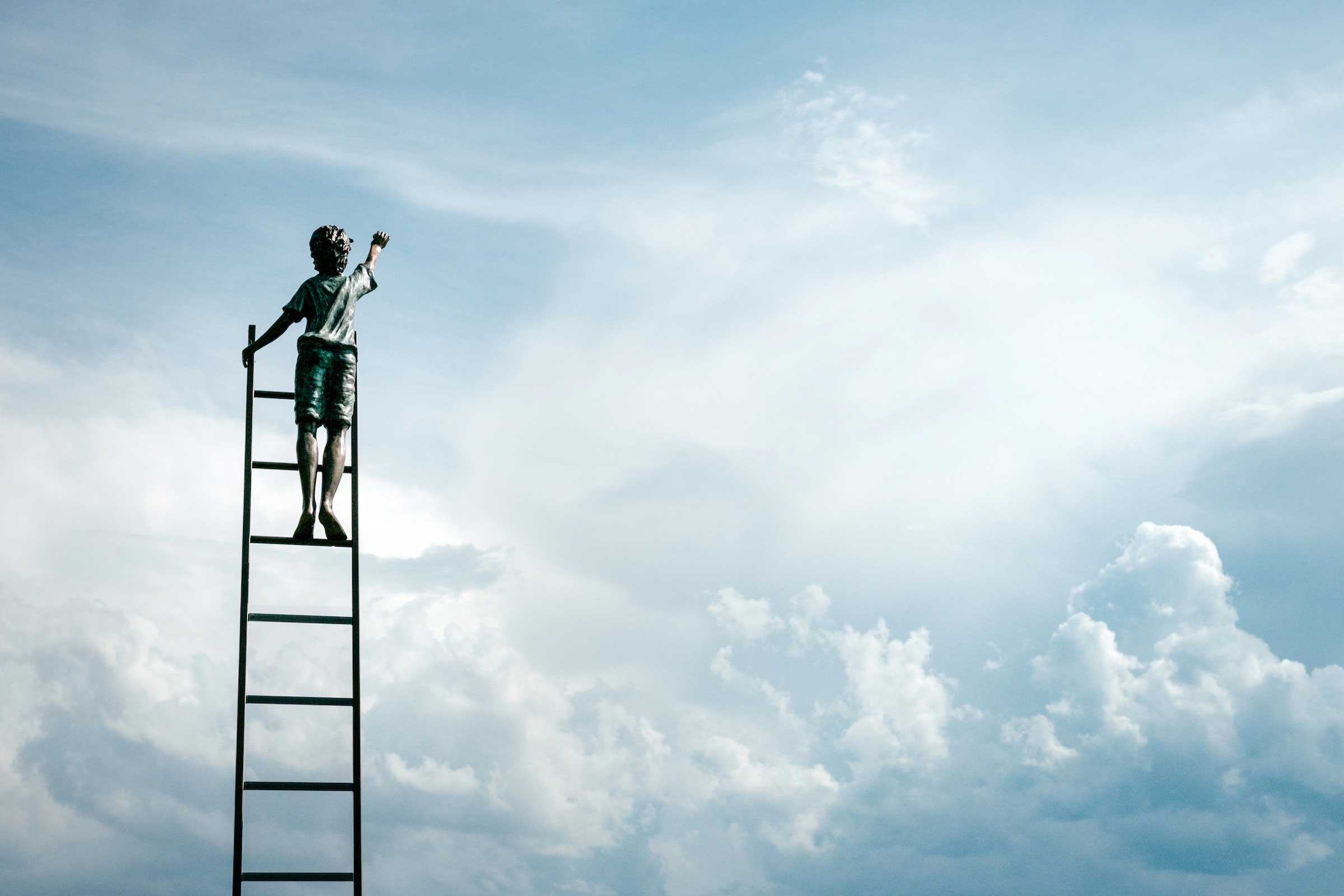 boy on a ladder reaching at clouds